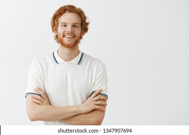 Indoor shot of friendly and carefree happy redhead guy with wavy hair in white polo shirt holding hands crossed on chest and smiling with joyful and entertained look obesring interesting perfomance