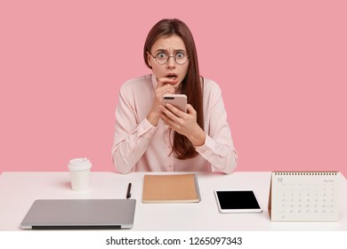 Indoor shot of frightened displeased woman holds mobile phone, has everything neatly arranged on table, recieves message, isolated over pink wall. Perfectionist lady at workplace with scared look