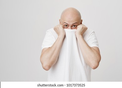 Indoor shot of funny bald caucasian man hiding head in his white t-shirt and glancing at camera while standing over gray background. Guy is embarrassed and trying to escape from people who look at him