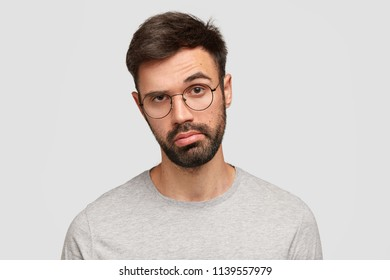 Indoor shot of good looking unshaven young male has bored hesitant expression, raises eyebrow in bewilderment, purses lips, makes decision, feels sick and tired of bachelorhood and being alone