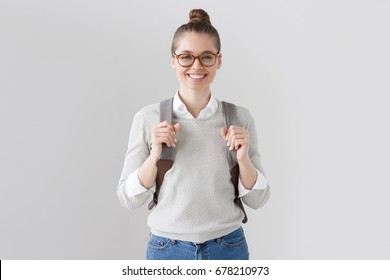 Indoor shot of good-looking active European female isolated on grey background wearing backpack and pulling forward its straps, looking right at camera, smiling friendly and openly, ready to chat.
