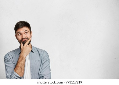 Indoor shot of handsome brunet male with pensive expression, dressed in fashionable shirt, tries to remember something, isolated over white background with copy space for your promotional text