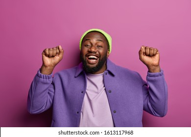 Indoor shot of handsome teenager with dark skin, beard, raises clenched fists, has fun and celebrates successfully passed examination session at university isolated on lilac background feels energized