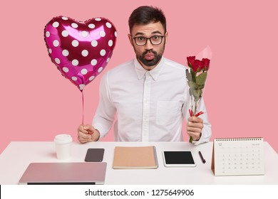 Indoor shot of handsome unshaven man pouts lips, carries valentine and bouquet, has romantic relationships in office, poses over pink studio wall, busy working, uses modern gadgets. Perfectionism