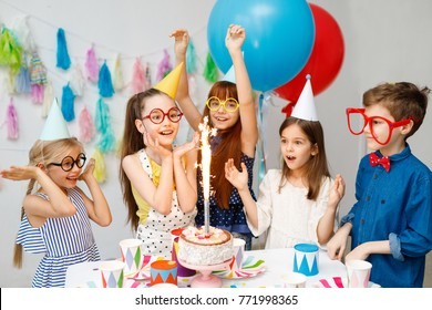 Indoor shot of happy joyful children look at big sparkle on cake, celebrate birthday, wear awkward big spectacles, party caps, stand near table with sweets in decorated room, have excited expressions