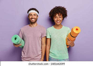 Indoor shot of happy mixed race female and male ready for fitness training, carry rolled up mats under arms, have glad faces, enjoy active life and everyday regular workout, wear casual sport clothes