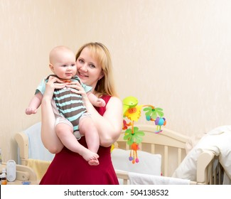 Indoor shot of happy mother holding smiling baby