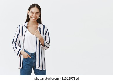 Indoor shot of happy sucessful young female entrepreneur in striped blouse and jeans, holding hand in pocket, smiling joyfully, being pleased after opening own business over gray background
