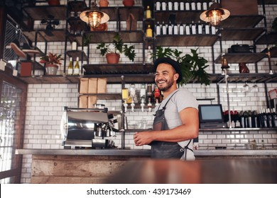 Indoor shot of happy young bar owner standing at the counter and looking away smiling