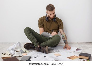 Indoor shot of hipster male with trendy hairstyle, thick berad and tattooed arms, looks attentively at book, writtes notes in notebook, being busy all day as prepares for entry exam to university