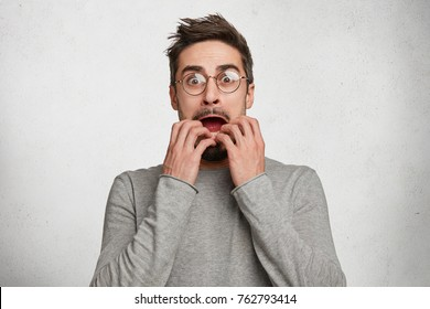 Indoor shot of horrified frightened hipster guy stares through spectacles, gestures actively and nervously, trembles from fear, has real fobia towards something, worries and afraids of darkness.