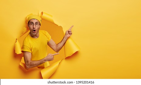 Indoor shot of impressed delighted unshaven man points away at upper right corner, poses through torn paper hole, wears yellow hat and t shirt, advertises awesome product. Advertisement concept