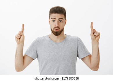 Indoor shot of interested and intrigued handsome masculine man with beard and brown hairstyle folding lips from amazement and curiosity raising index fingers pointing up questioned over gray wall