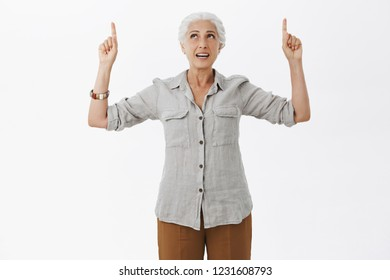 Indoor shot of intrigued and curious charming senior woman with gray hair in casual shirt raising arms looking and pointing up standing interested over white background