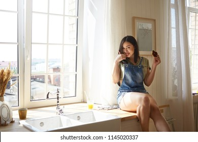 Indoor shot of joyful charming young chubby female with big hips sitting on windowsill in kitchen, gourmandizing, enjoying tasty doughnut, licking fingers. Happy girl eating delicious junk food