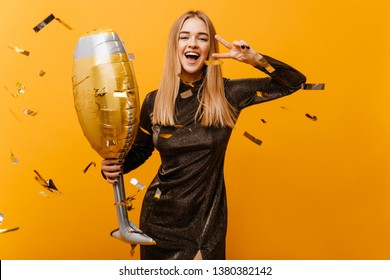 Indoor shot of laughing winsome woman with wineglass posing on yellow background. Gorgeous birthday girl in dress standing under confetti and laughing.