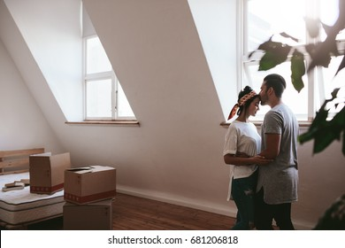 Indoor shot of loving young couple moving into their new home. Man and woman in love standing together with cardboard boxes in room.