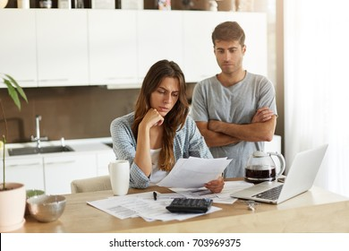 Indoor shot of married couple doing paperwork at home: serious female in shirt reading information in sheet of paper with frustrated look while her husband standing behind her, keeping arms folded