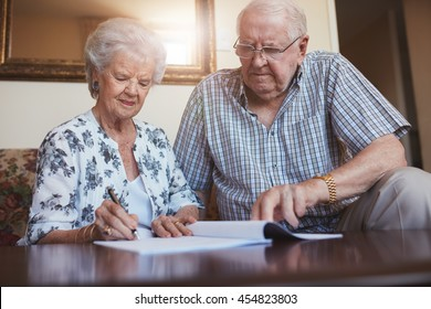 Indoor shot of mature couple at home signing documents together. Senior man and woman sitting on sofa doing retirement paperwork.