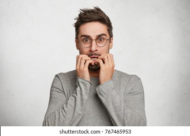 Indoor shot of nervous worried handsome man bites fingers, being scared of horror film or afraid of exams, has frightened expression, isolated over white concrete background. Emotional adult