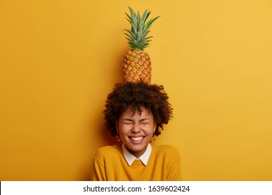 Indoor shot of overjoyed Afro American woman carries pineapple on head, closes eyes and smiles broadly, has fun with tropical fruit, isolated over yellow bright background. People, emotions concept
