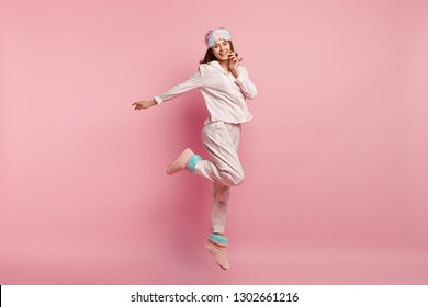 Indoor shot of overjoyed European woman raises leg, spreads hand, wears casual pyjamas and eyemask, smiles happily, isolated over pink background, enjoys bed time and good rest during weekend