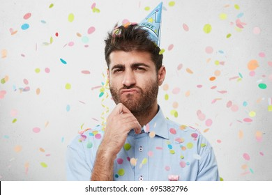 Indoor shot of pensive bearded guy in light blue shirt and party cap, keeping his hand under chin, having gloomy expression, realizing that not all his friends coming to party. Sullen man on birthday