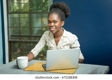 Indoor shot of a pensive black woman at her computer with a cup of coffee or tea on a shabby chic concrete countertop kitchen