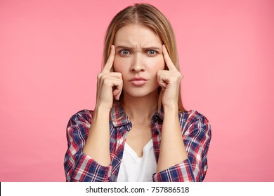 Indoor shot of pensive female model tries to concentrate or remember important information, had bad memory, has thoughtful expression. Female student answers on exam, recollects topic in mind