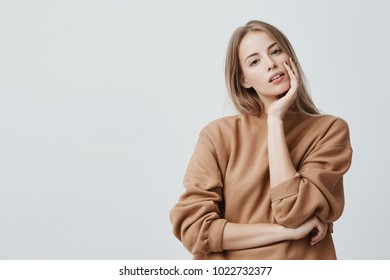 Indoor shot of pleasant looking attractive blonde woman dressed in beige loose sweater with appealing dark eyes and parted lips, poses against gray studio wall. Beauty and youth concept