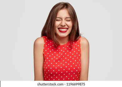 Indoor shot of pleasant looking pleased young European woman with joyful expression, giggles positively, dressed in polka dot dress, poses against white background. Happiness and beauty concept