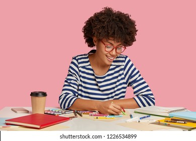 Indoor shot of pleased artist holds crayon, makes sketches on blank sheet of paper, has positive expression, dressed casually, wants to create real masterpiece, isolated over pink background