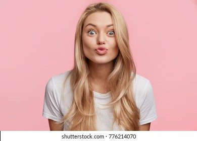 Indoor shot of pleased attractive woman rounds lips as going to kiss with boyfriend, has happy expression as spends free time with lover, makes grimace. People, body language and facial expressions