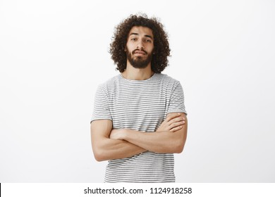 Indoor shot of popular handsome male model with beard and afro hairstyle, holding hands crossed on chest and looking with raised chin at camera, being confident and stubborn, standing over gray wall