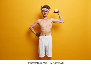 Indoor shot of positive man holds heavy sport equipment, enjoys workout in own gym, has skinny body, wants to be healthy and fit, wears transparent glasses, sport gloves, poses over yellow wall