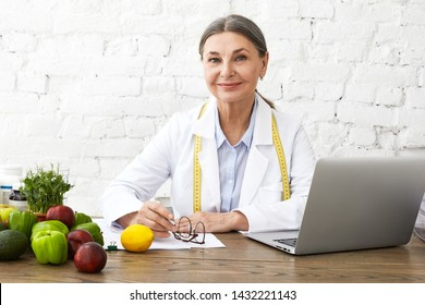 Indoor shot of positive smiling Caucasian female nutritionist in her sixties working online, sitting in front of open laptop pc, consulting clients on nutrition via social networks, making notes