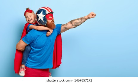 Indoor shot of powerful dad in protective helmet carries small child on back, play superhero game, fly together and make good things for people, isolated on blue background. Childhood, parents concept
