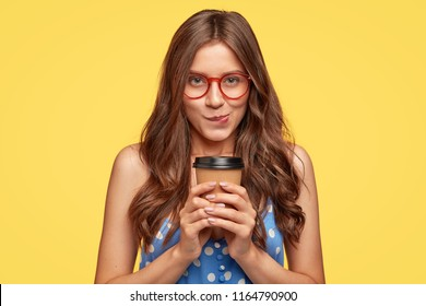 Indoor shot of pretty girl with intriguing expression, purses lower lip, holds paper cup of coffee, waits for suggestion from guy to date, wears round spectacles, isolated over yellow background
