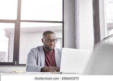 Indoor shot of professional black male freelancer works remotely on laptop computer, plans working schedule, keyboards information, focused into screen. Trader analyzes financial market online