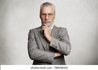 Indoor shot of prosperous experienced elderly wrinkled businessman dressed in grey formal suit, keeps hand under chin, comes for business meeting, isolated over white studio concrete background.