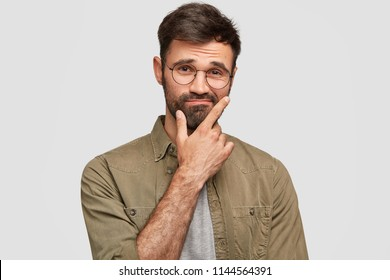 Indoor shot of puzzled hesitant unshaven guy holds chin and doubts, raises eyebrows, has clueless expression, wears stylish shirt, isolated over white background. People, emotions, lifestyle concept