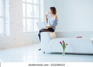 Indoor shot of romantic thoughtful mature European woman in stylish elegant clothes, having dreamy look, sitting in sofa with cup of tea or coffee with open laptop in front of window.
