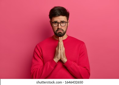 Indoor shot of sad pleading man says sincere please, makes praying gesture, request and apologizes from heart, wears red sweatshirt, models over pink wall, begs and looks with upset look at camera