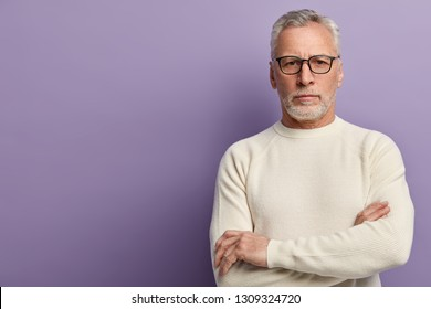 Indoor shot of self confident man with thick stubble, keeps hands crossed, wears transparent spectacles and white sweater, looks directly at camera, isolated over purple background with empty space