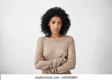 Indoor shot of skeptical young mixed race woman feeling suspicious, her look expressing disapproval or doubt, keeping arms crossed while having a suspicion that her husband cheated on her. Horizontal