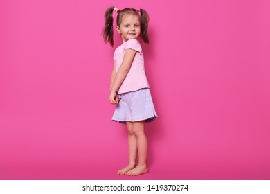 Indoor shot of small child with two pony tails and many colourful scrunchies, glad to be photographed in photo studio, charming kid looks at camera and smiles. Children and childhood concept.