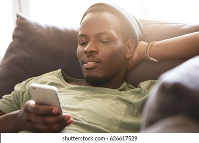 Indoor shot of smiling black young man surfing internet on mobile phone, messaging friends online and checking newsfeed via social media while relaxing at home, lying on couch with hands behind head