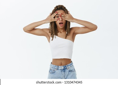 Indoor shot of stylish and slim good-looking African American woman with dreadlocks in white top covering sight with hands peeking with one eye through fingers intrigued and interested