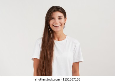 Indoor shot of stylish young woman, wears her messy dark hair to the side, smiles broadly, feels happy. Wears casual white t-shirt