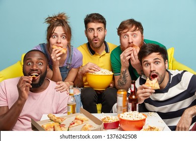 Indoor shot of surprised mixed race friends, eat popcorn, pizza, have fearful panicked faces, enjoy watching horror films, have free time on evening weekend, sit on sofa. People and free time concept
